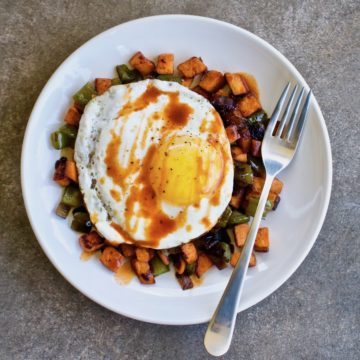 Overhead view of chipotle sweet potato hash with a fried egg and a fork