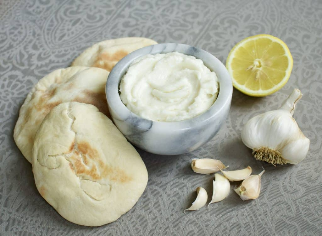 Lebanese garlic sauce (toum) in a small bowl surrounded by garlic, pita bread, and a lemon