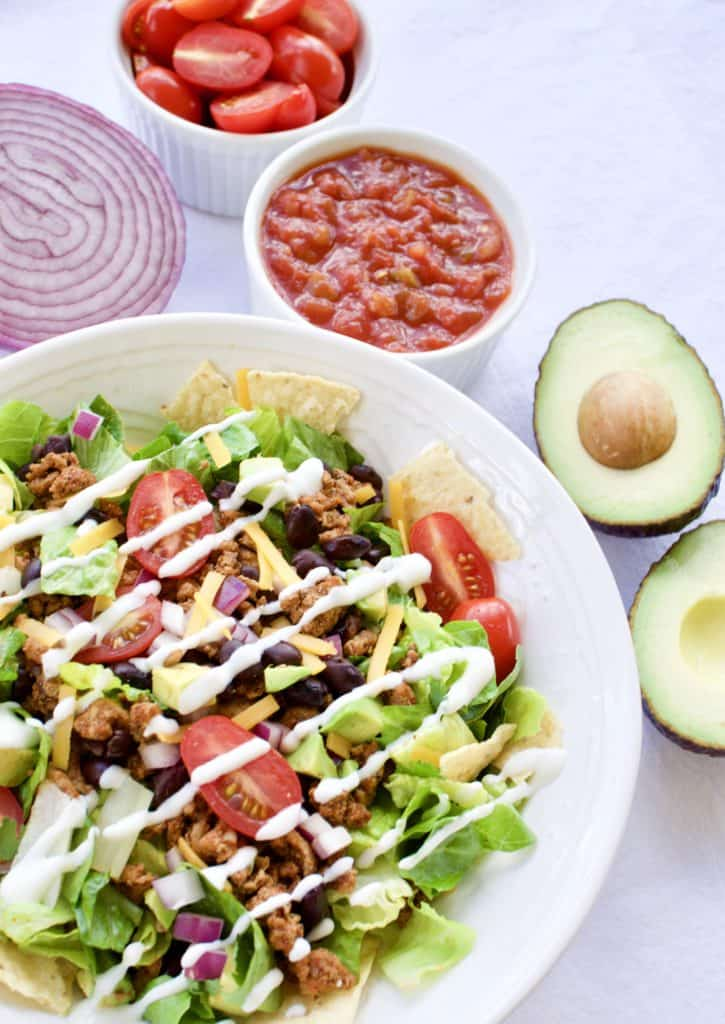 Taco salad in a white bowl surrounded by ingredients
