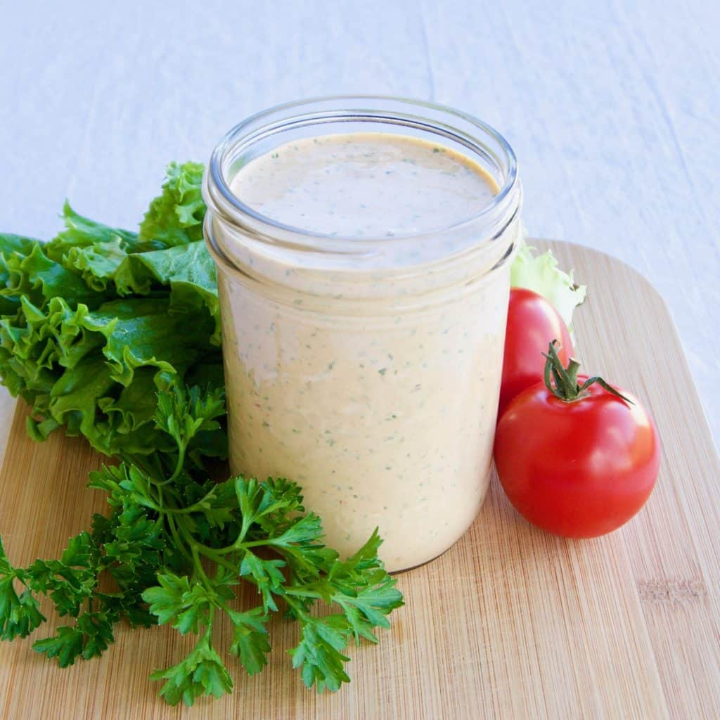 Magical chipotle ranch dressing in a mason jar surrounded by greens and fresh tomatoes