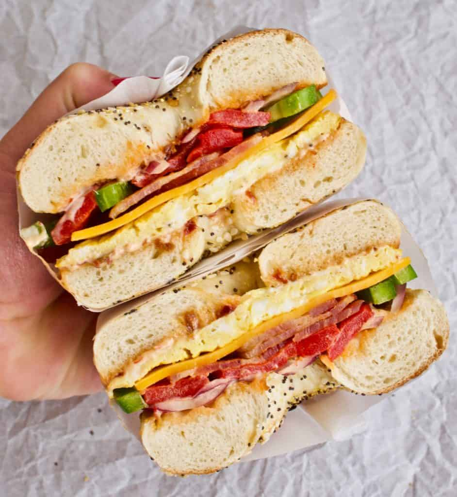Hand holding two halves of a Copycat Bruegger's Western Bagel