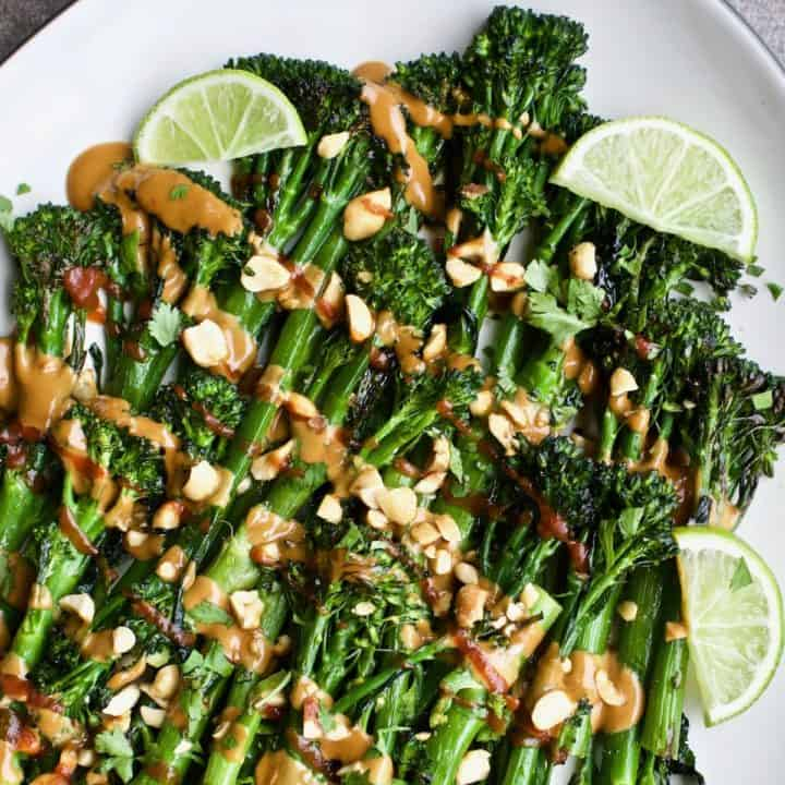Roasted broccolini with spicy peanut sauce arranged on a plate