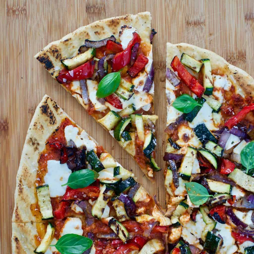 Overhead view of grilled veggie pizza with slice pulling away