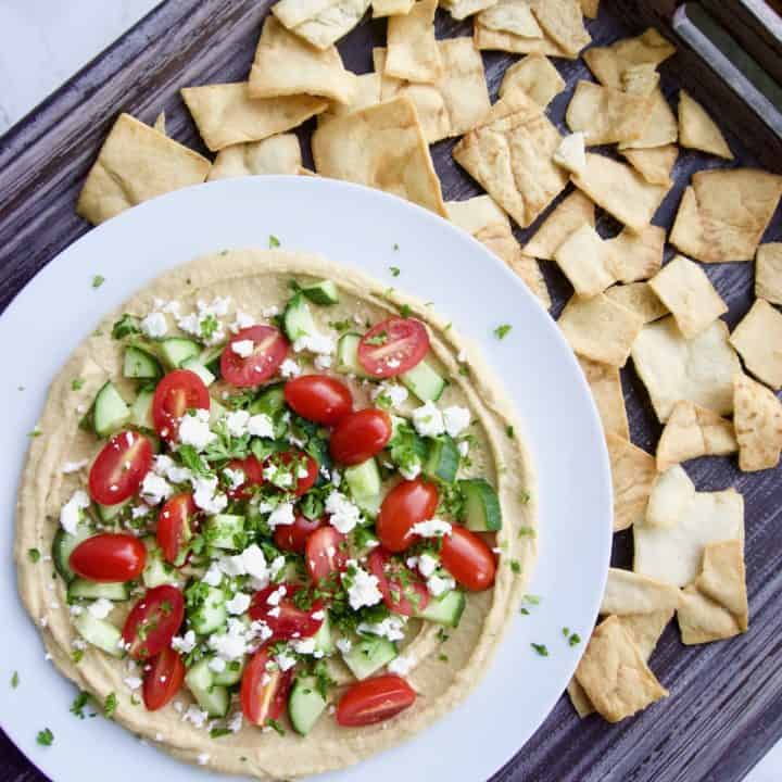 Mediterranean layer dip in a bowl with pita chips nearby