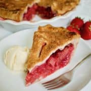 Slice of Strawberry Rhubarb Pie on a white plate with scoop of vanilla ice cream and fork
